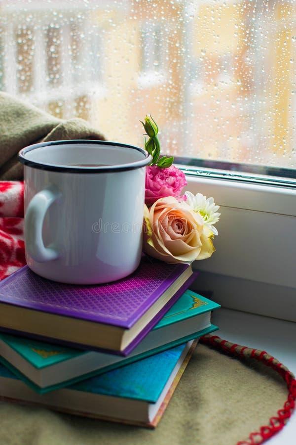 Vida inmóvil acogedora: taza de té, de libros y de flores calientes con la tela escocesa caliente en alféizar Día lluvioso afuera foto de archivo libre de regalías