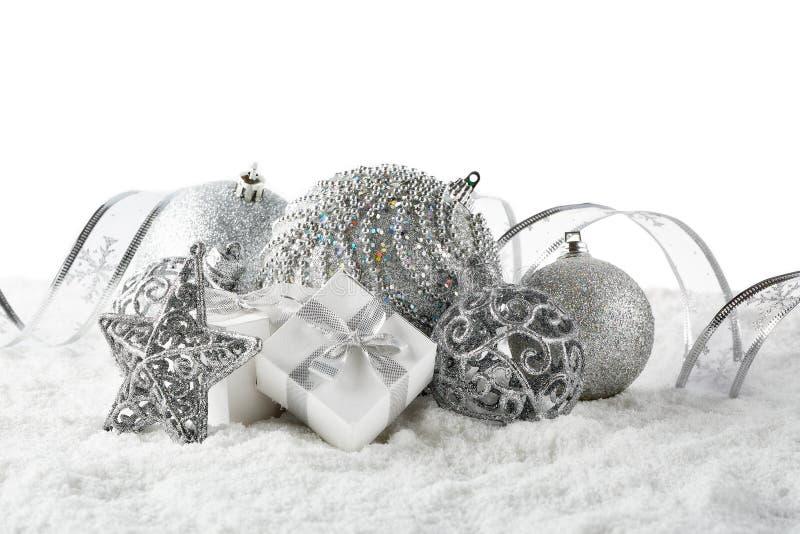 Vida inmóvil de la Navidad con las cajas de plata de las bolas, de la estrella y de regalo que mienten en nieve del invierno en u imágenes de archivo libres de regalías
