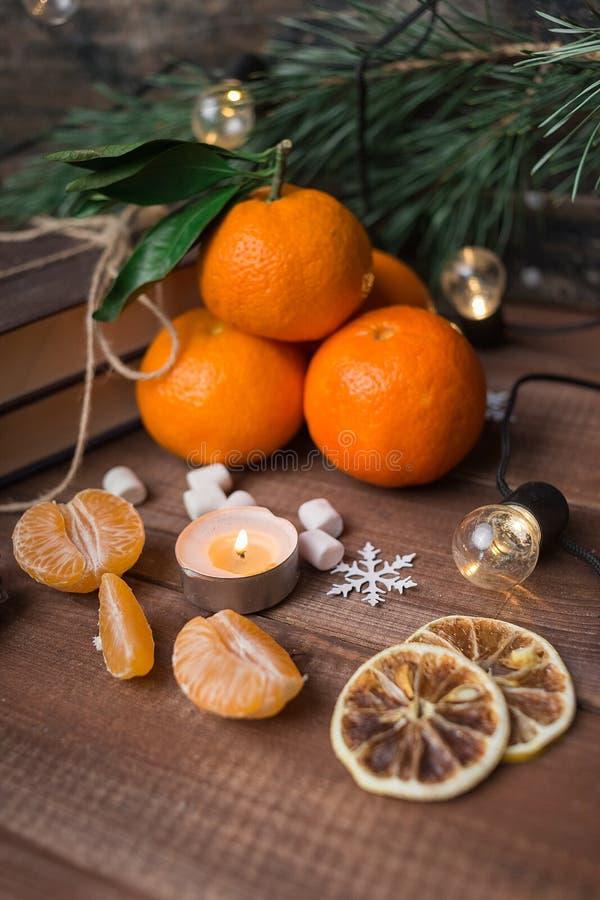 Vida inmóvil de la Navidad con los mandarines, las melcochas, la guirnalda y el copo de nieve frescos en fondo de madera fotografía de archivo
