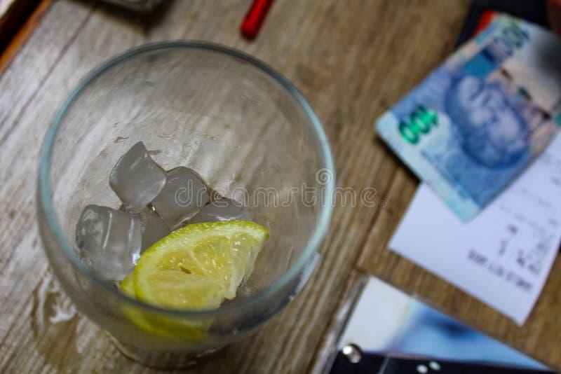 Vida inm?vil del restaurante - el resto de una bebida, de que significa los cubos de hielo y la rebanada de lim?n en una tabla co fotografía de archivo