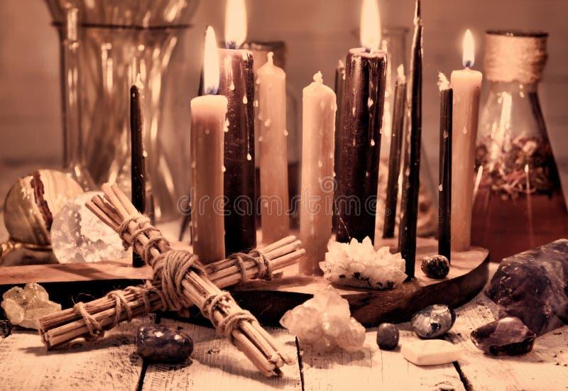 Vida inmóvil del vintage con la cruz, las velas negras, los minerales y los frascos en la tabla imagen de archivo libre de regalías