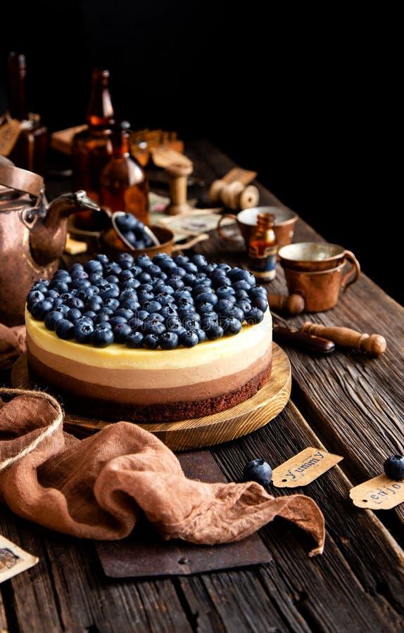 Vida inmóvil hermosa con el pastel de queso delicioso hecho en casa de tres chocolates en soporte de madera en la tabla rústica fotos de archivo libres de regalías
