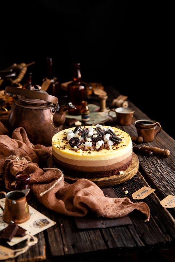 Vida inmóvil hermosa con el pastel de queso delicioso hecho en casa de tres chocolates en soporte de madera en la tabla rústica imagen de archivo libre de regalías