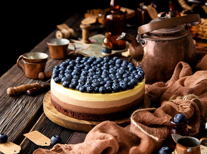 Vida inmóvil hermosa con el pastel de queso delicioso hecho en casa de tres chocolates en soporte de madera en la tabla rústica imagenes de archivo