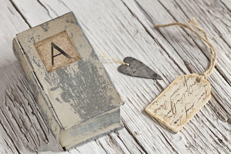 Vida inmóvil nostálgica con poca caja de la lata con la letra A y el corazón imagenes de archivo