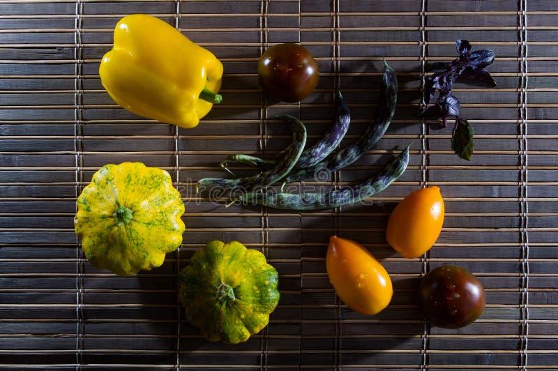 Vida residual del otoño - calabaza pequeña manchada, judías espárragos, albahaca morada, paprika, tomates amarillos y chocolate e imágenes de archivo libres de regalías