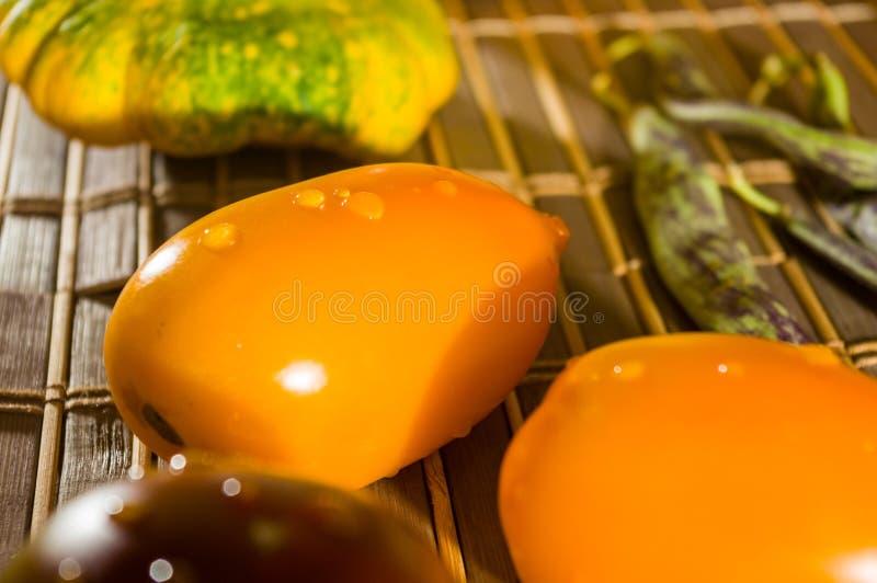 Vida residual del otoño - calabaza pequeña manchada, judías espárragos, albahaca morada, paprika, tomates amarillos y chocolate e fotografía de archivo