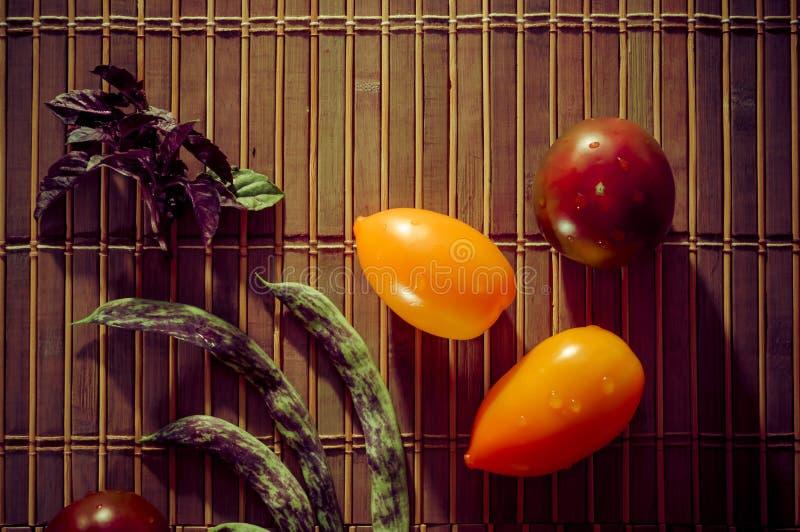 Vida residual del otoño - calabaza pequeña manchada, judías espárragos, albahaca morada, paprika, tomates amarillos y chocolate e fotos de archivo