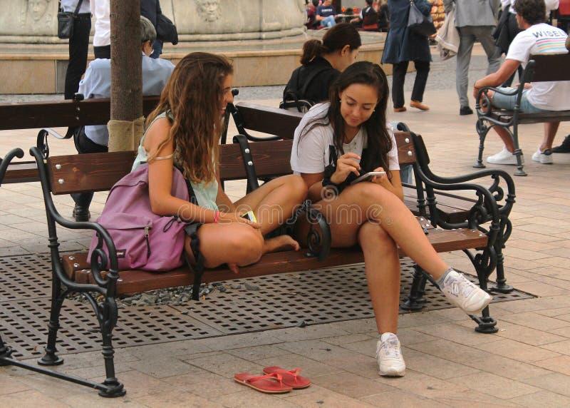 Vida social - dos muchachas bonitas jovenes que se sientan en un banco imagen de archivo