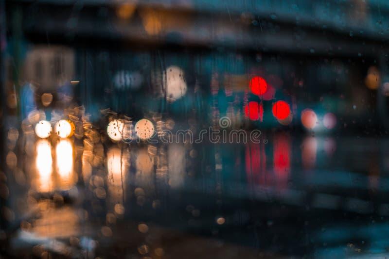 Vida urbana da noite através do para-brisa: carros, luzes e chuva fotografia de stock royalty free