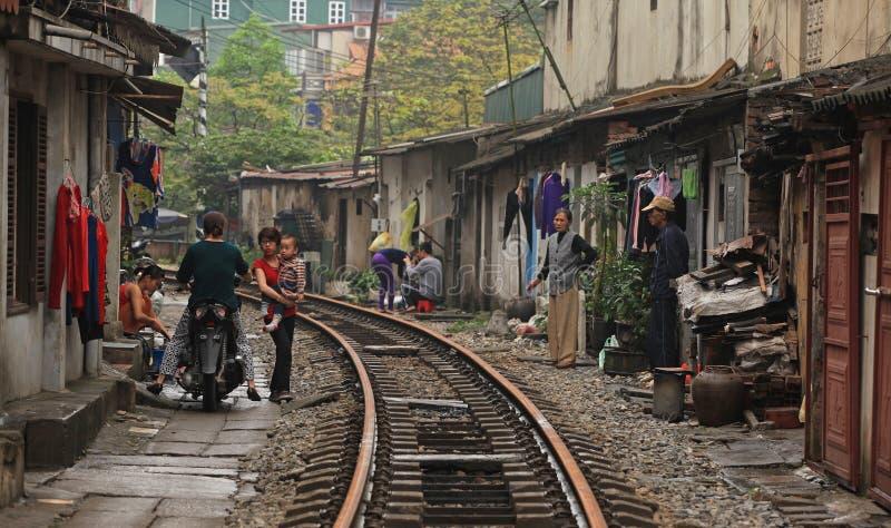 Vida usual y casas en la pista ferroviaria foto de archivo