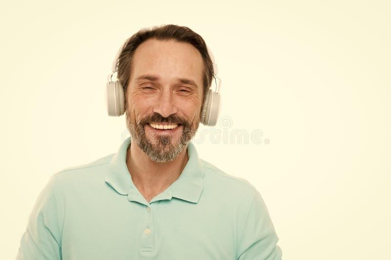 Vida viva ruidosamente Hombre maduro en auriculares est?reos Hombre barbudo feliz que escucha la m?sica v?a los auriculares No ha imágenes de archivo libres de regalías