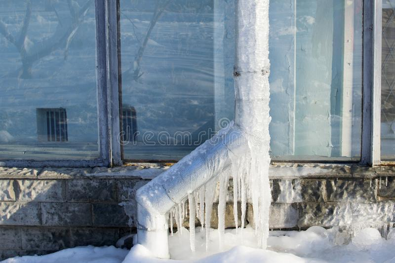 Vidangez dans la glace sur la rue en hiver est complètement gelé image libre de droits