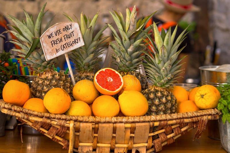 Vide- korg med apelsiner och ananors royaltyfri fotografi