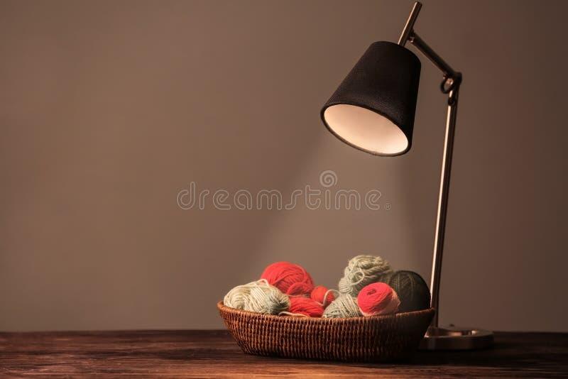 Vide- korg med att sticka trådar och lampan på grå bakgrund arkivfoton