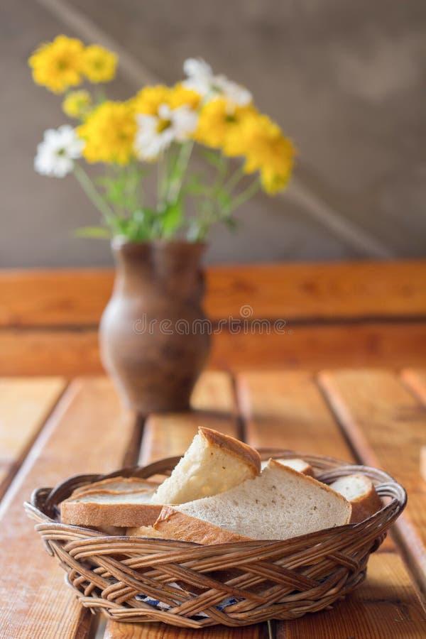 Vide- korg med bröd och blommor royaltyfria bilder