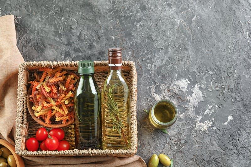 Vide- korg med flaskor av olivolja, pasta och tomater på grå bakgrund fotografering för bildbyråer