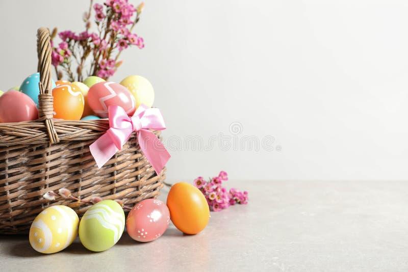 Vide- korg med målade påskägg och blommor på tabellen arkivfoto