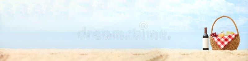 Vide- korg med mat och vin på sand nära havet Strandpicknick royaltyfria bilder