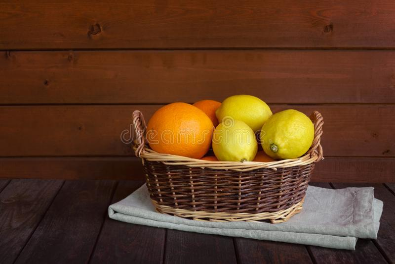 Vide- korg med nya mogna apelsiner och citroner på den åldriga trätabellen royaltyfri foto