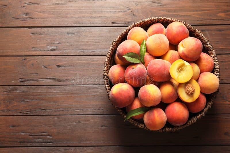 Vide- korg med nya söta persikor på trätabellen royaltyfria foton