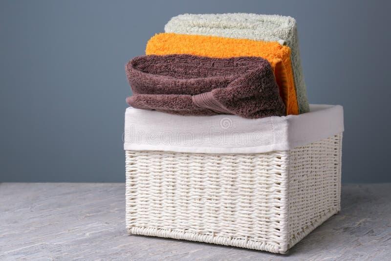 Vide- korg med vikta rena handdukar på tabellen royaltyfri fotografi