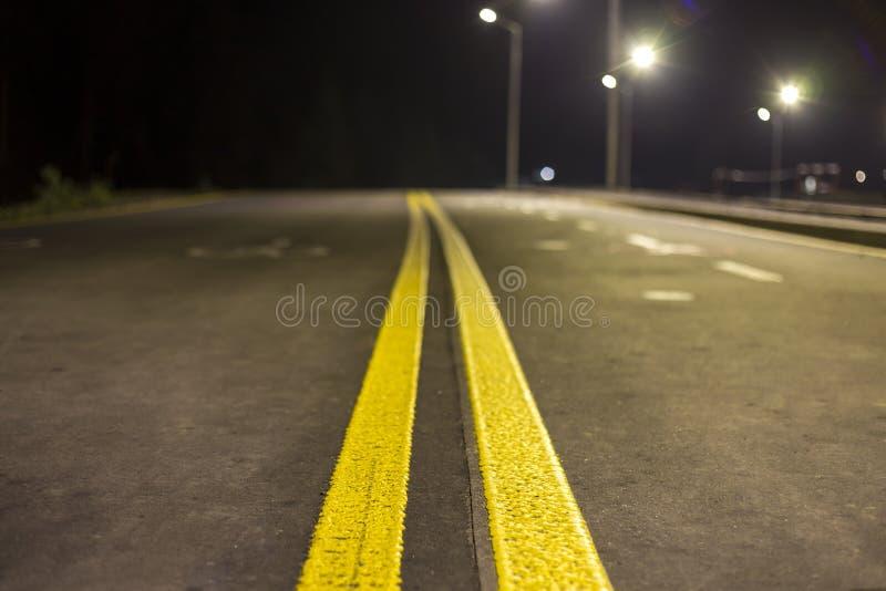 Vide lisse moderne large illuminé avec la route d'asphalte de réverbères avec la ligne de repérage blanche lumineuse de signe la  images libres de droits