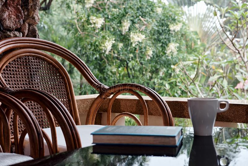 Vide- stol på balkong, koppen kaffe och boken arkivfoto