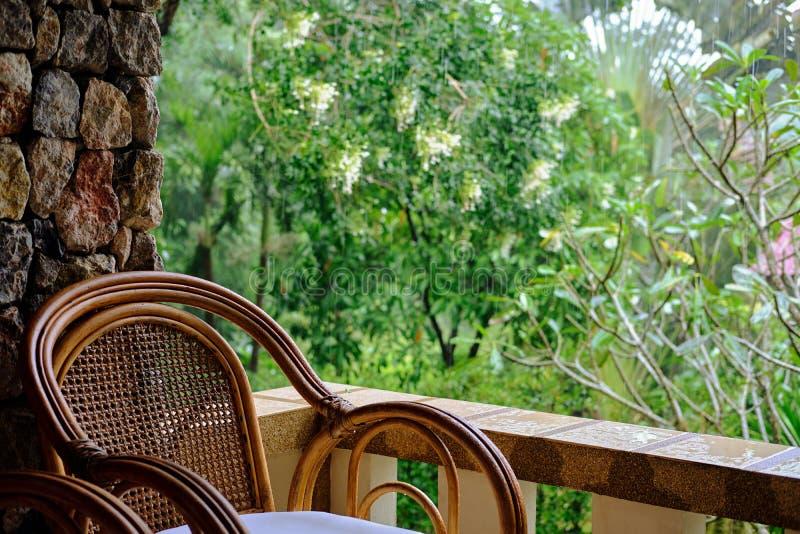 Vide- stol på balkong, koppen kaffe och boken arkivbilder