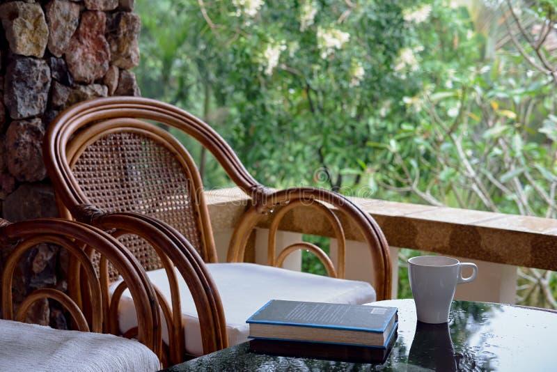 Vide- stol på balkong, koppen kaffe och boken fotografering för bildbyråer
