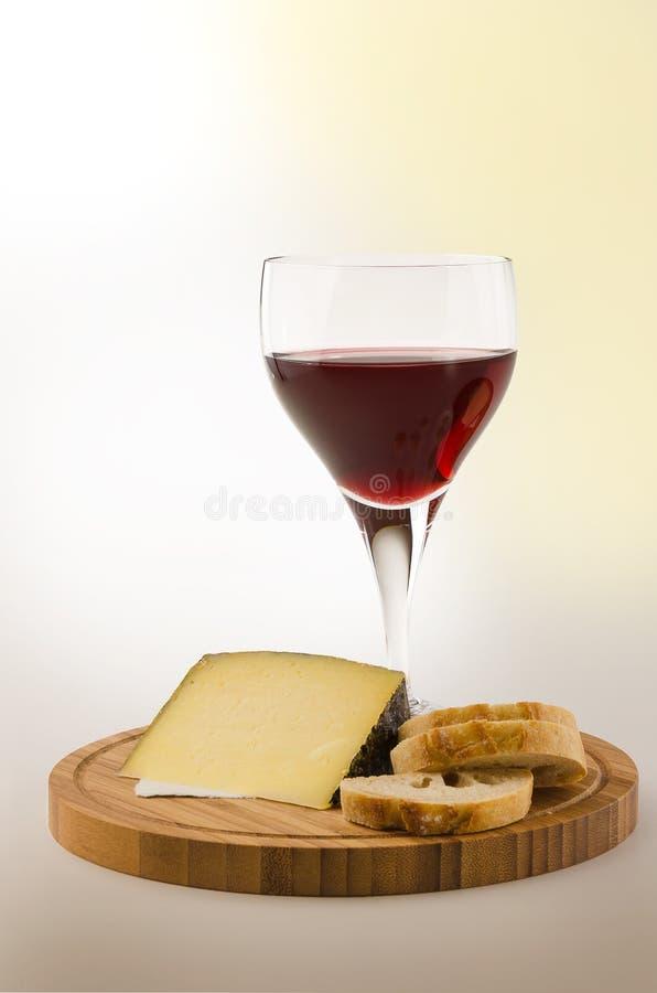 Videira vermelha em um vidro com queijo e pão 1 foto de stock royalty free