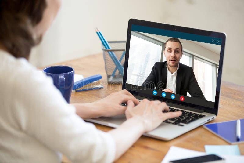 Video appell för affärskvinnadanande till affärspartnern som använder bärbara datorn arkivfoto