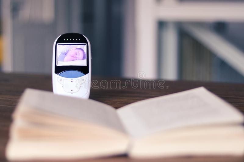 Video baby monitor with image of sleeping baby on the screen on the table with open book. Mother relax time during child daytime s. Leep. Baby security and stock photography