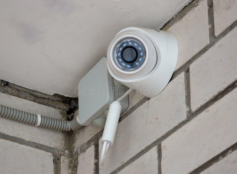 Video bevakningkamera på en tegelstenvägg royaltyfri bild