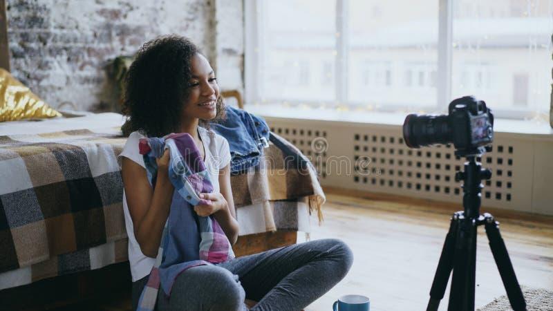 Video blog della corsa mista della registrazione allegra della donna circa il suo guardaroba per il viaggio con la macchina fotog fotografia stock libera da diritti