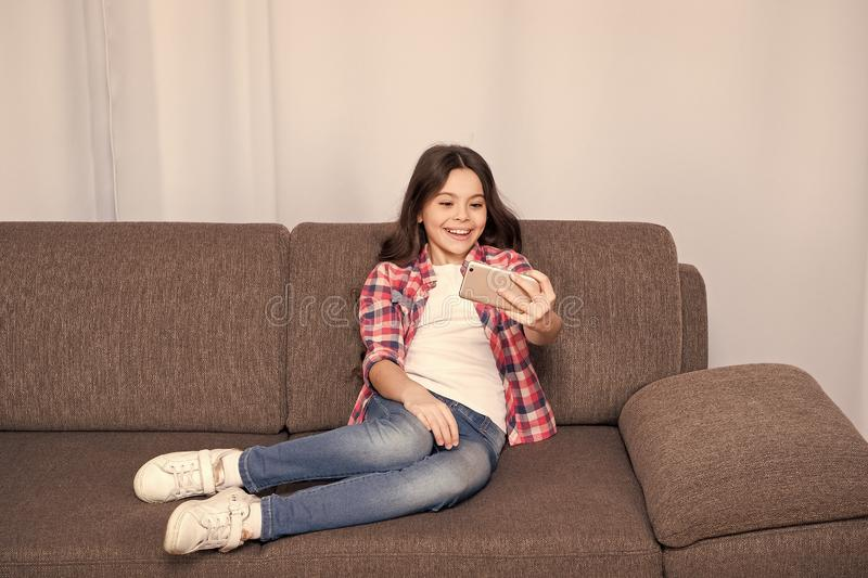 Video call concept. Child relaxing on couch and communicate online. Girl hold smartphone taking selfie. Selfie for. Social networks. Let me take selfie. Child royalty free stock images