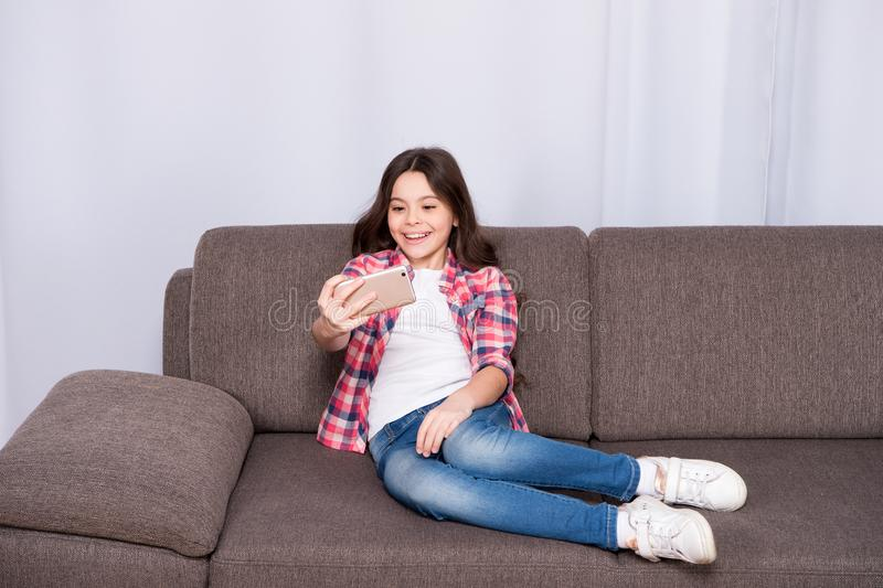 Video call concept. Child relaxing on couch and communicate online. Girl hold smartphone taking selfie. Selfie for. Social networks. Let me take selfie. Child stock photo