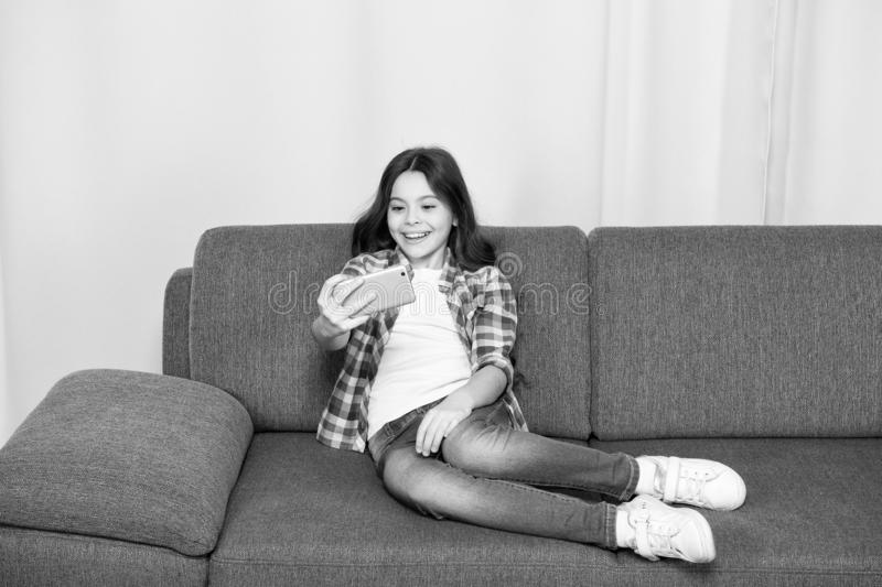 Video call concept. Child relaxing on couch and communicate online. Girl hold smartphone taking selfie. Selfie for. Social networks. Let me take selfie. Child stock images
