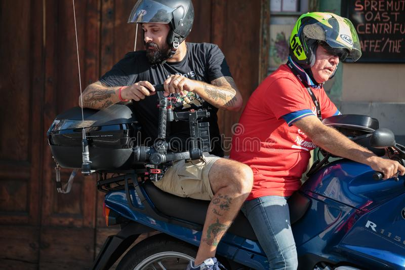 Video Camera Operator on a Motorcycle with a Camera while Filming a Sporting Event stock image