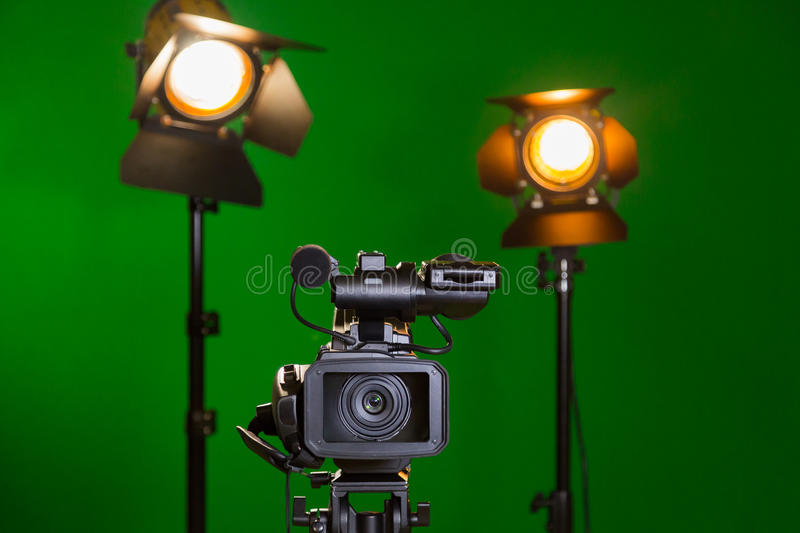 A video camera and a spotlight with a Fresnel lens on a green background. Filming in the interior. The chroma key.  stock photo