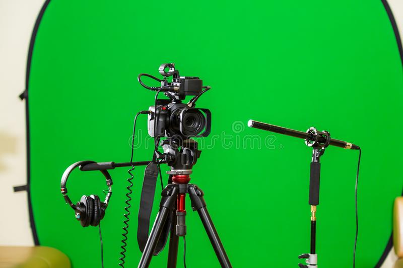 Video camera on a tripod, headphones and a directional microphone on a green background. The chroma key. Green screen royalty free stock photography