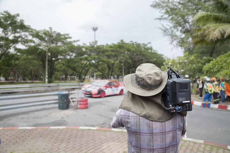 Video cameraman operator Racing car in a racetrack.  stock photo