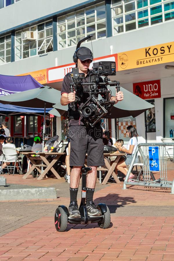 Video cameraman riding on Segway. A cameraman shooting an event while riding on a personal transporter for smooth movement. The camera in his large camera royalty free stock photos