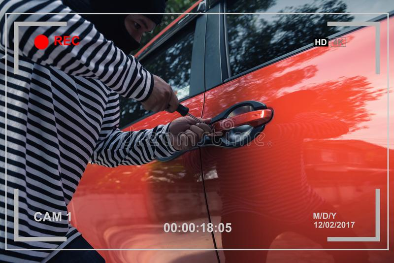 Video capturing car thief trying to unlock a car by screwdriver royalty free stock image