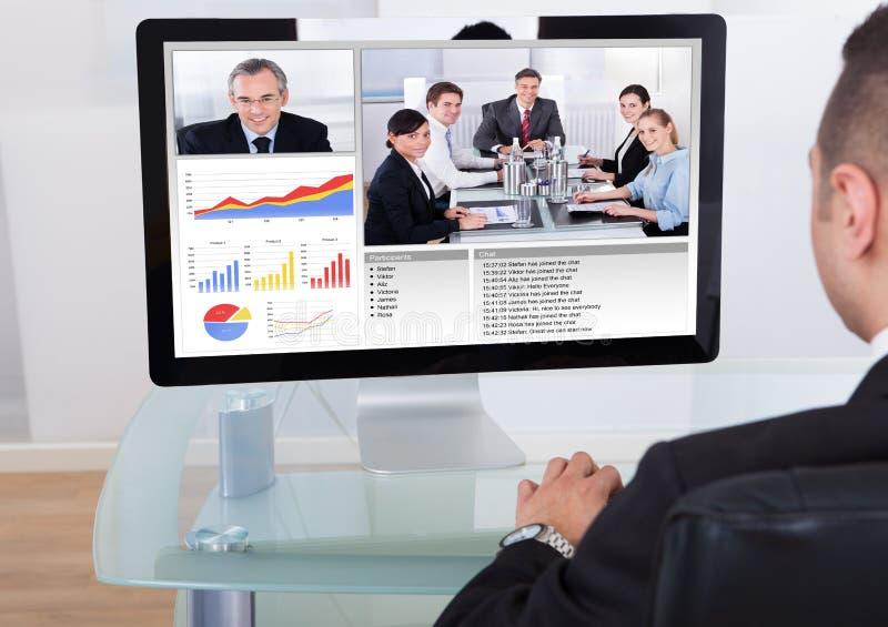 Video comunicazione dell'uomo d'affari con il gruppo fotografie stock