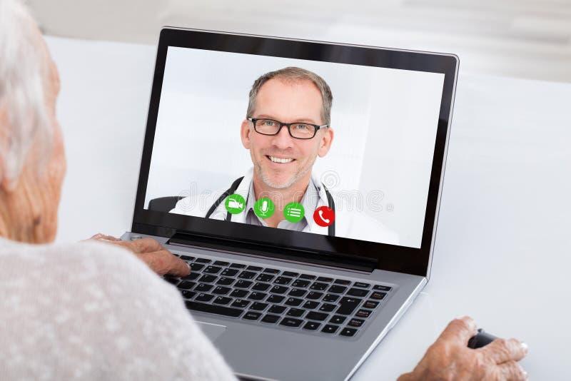Video comunicazione senior della donna sul computer portatile fotografia stock