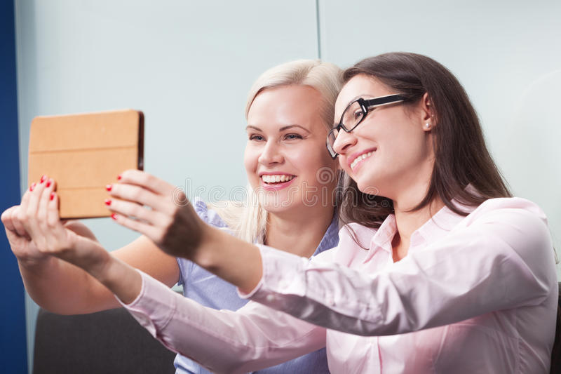 Video conference. Two attractive women having video conference using tablet stock photo