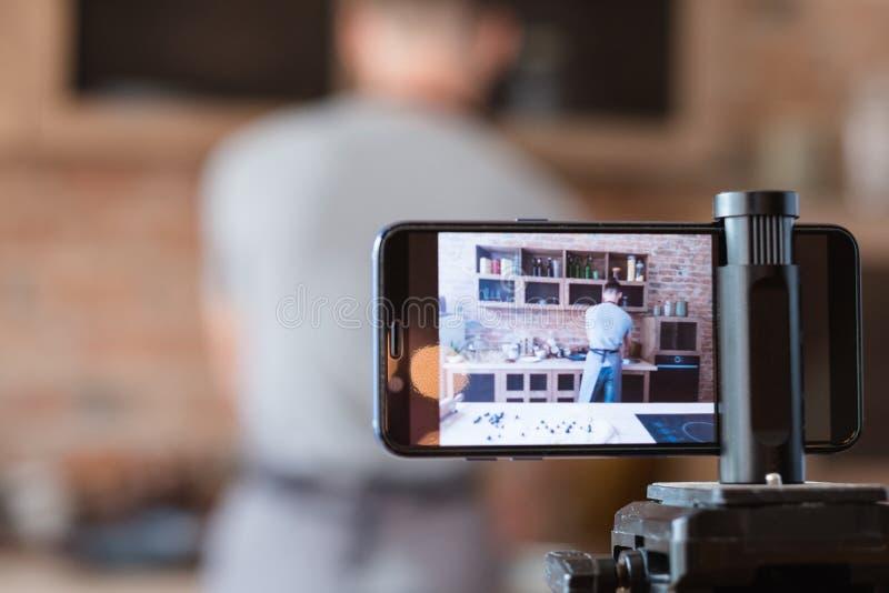 Video cucina dell'uomo della macchina fotografica del telefono del tiro di tecnologia fotografia stock libera da diritti