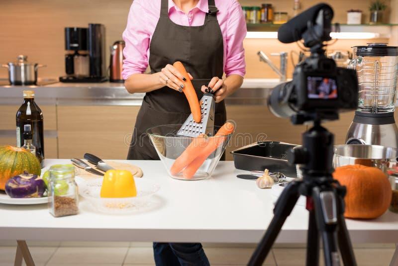 Video della registrazione della donna di lei che cucina per il video blog online fotografia stock