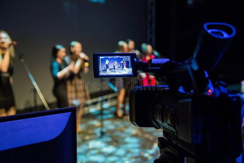 Video des Konzerts Mädchen singen in den Mikrophonen Kamerarecorder mit LCD-Anzeige Schießen im Innenraum stockfotografie